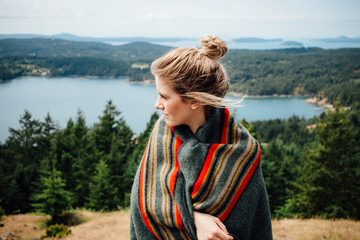 Young Blonde Woman Wrapped In Wool Blanket On Forest Island Hillside