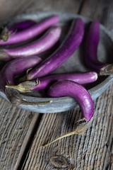 Fresh purple eggplants inside tray on wooden table