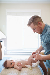 Young man giving baby a diaper change on floor