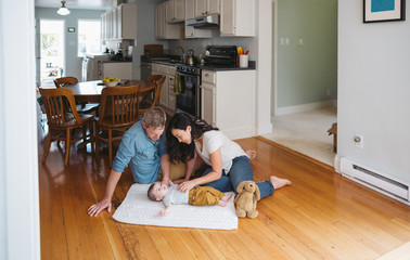 Young parents playing with baby lying on old wood floor