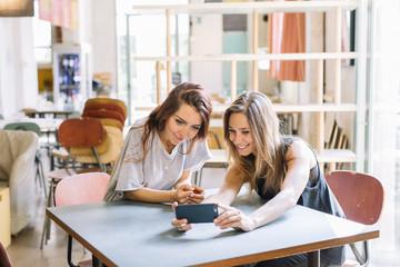 Two happy friends make a selfie in a coffee shop