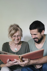 Beautiful senior woman and young man watching photo album