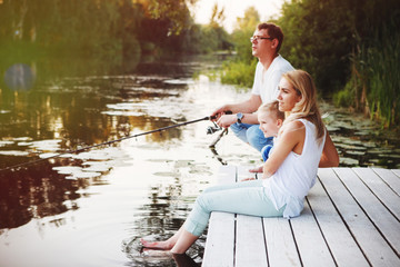 Young happy family with kids fishing in pond in summer