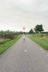 Back view of a little girl with pink balloon walking on a long road