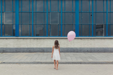 Barefoot little girl in white dress with pink balloon in front of old building