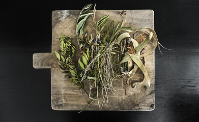 Dried Herbs and flowers lying on chopping board in kitchen