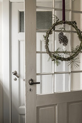 A Christmas wreath with pinecones on a door in a house