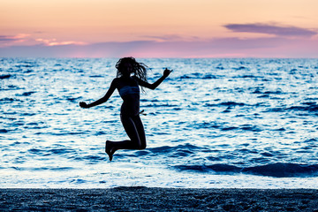 Young Woman Jumps at Twilight on the Beach