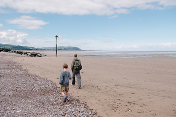 Father and son walking along the beach