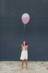 Smiling little girl with a single pink balloon against a dark wall