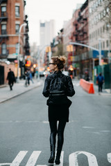 Blond woman walking down the street in NYC, back view.