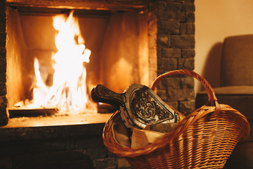 Fototapete - Burning fireplace and basket with firewood. Winter holiday concept