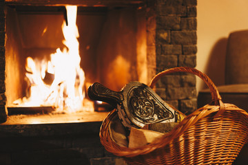 Fototapete - Basket with vintage bellows in front of a burning fireplace