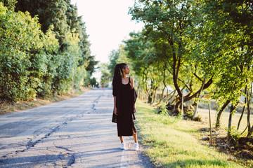 Woman with dreadlocks posing on rural road