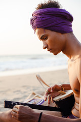 Portrait of a young man on the beach Indian musical instrument tuning