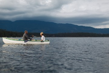 Mature couple rowing together on lake