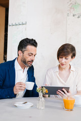 Two colleagues sitting in a cafe with tablet