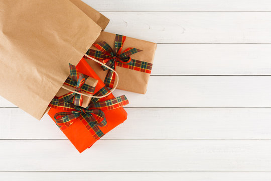 Creative christmas gifts in paper bag on white wood table background