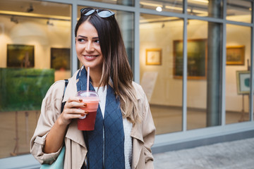 Beautiful Brunette Woman Standing on a Street While Having Smoothie