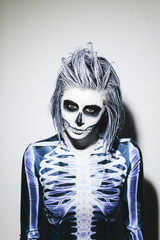 Spooky portrait of woman with skeleton costume and halloween make up on white wall
