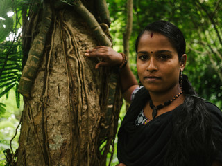 Indian girl leaning towards tree in jungle