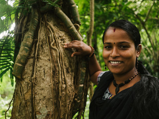 Happy Indian girl leaning towards tree in tropical forest