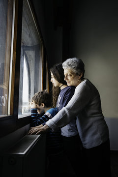 Two kids waiting by the window together with grandma