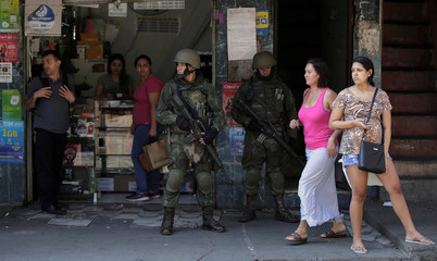 Residents walk next to a member of the armed forces during an operation against drug gangs in the Rocinha slum in Rio de Janeiro
