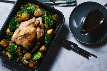 Roast chicken dinner served in roasting tray with gravy boat