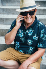 Stylish senior man talking on the phone, smiling, wearing a straw hat and sunglasses and sitting on stairs