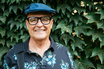 Hipster senior man portrait smiling with a beret and glasses in front of an ivy background
