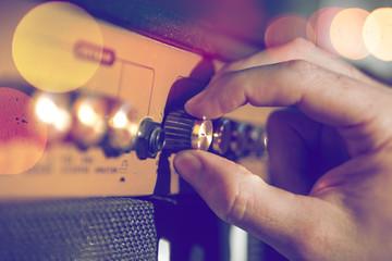 Detalle de mano de musico y amplificador.Ingenieria de sonido y produccion musical.