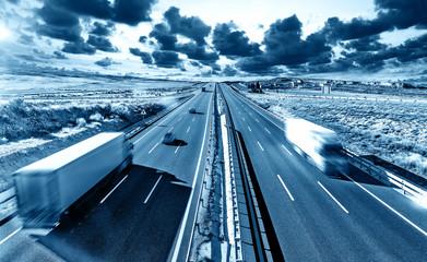 Camiones y autovia.Transporte internacional y logistica.Mercancia llegando a su destino por carretera.
