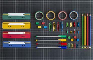 Multicolored office tools on dark background
