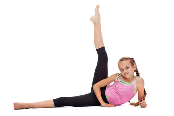 Young girl doing gymnastic exercises for leg strength and flexibility