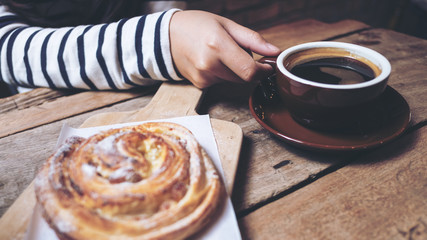 Closeup image of a raisin danish and a woman holding and drinking hot coffee on wooden vintage table in coffee shop