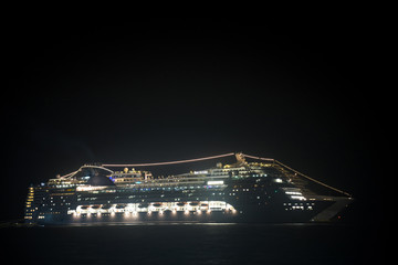 A huge cruise ship at night stands at anchor glowing with very bright lights