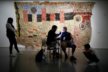 """Gabi Shoval, who lost his leg during military combat while serving as a soldier in the Israeli army, gets a tattoo done by Israeli artist Alexey Zamotevsky as part of the """"Healing Ink """" project, at the Israel Museum in Jerusalem"""