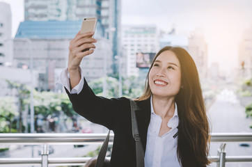 businesswoman attractive happy and smile using smartphone camera selfie outdoor on break time of working.