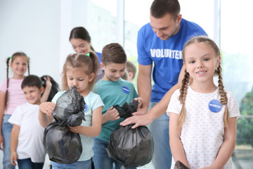 Happy volunteers and children with garbage bags indoors