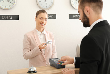 Businessman paying for hotel room at reception