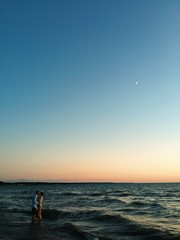 A young couple swimming at the beach at sunset