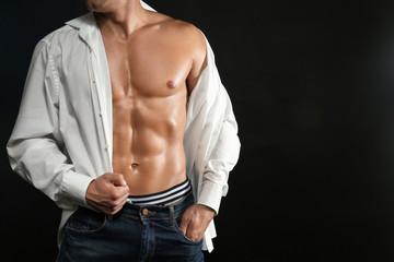 Sexy muscular man in unbuttoned shirt on dark background
