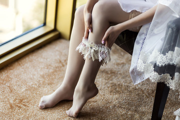 Morning of the bride, the bride wears a wedding garter on leg, a wedding, a beautiful dress