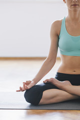 Young woman meditating at home, practicing yoga