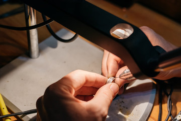 Goldsmith repairing a wedding ring with a welding machine