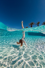 Over under image of a teenage girl floating head down in a large swimming pool