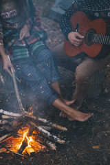 Couple of tourists playing guitar near bonfire