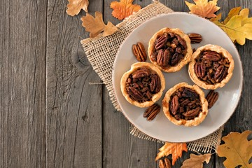 Plate of mini pecan pie tarts, rustic overhead table scene on a wood background