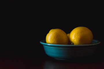 Lemons in a blue bowl against a dark background.
